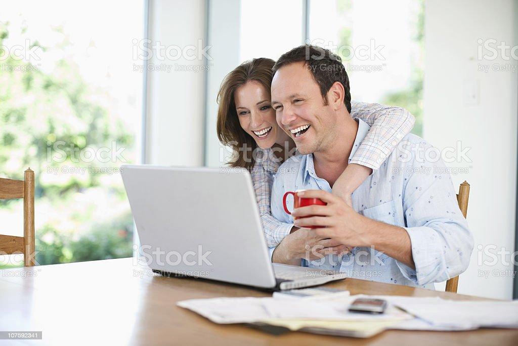 Glückliches Paar mittleren Alters, die auf laptop zu Hause - Lizenzfrei 30-34 Jahre Stock-Foto