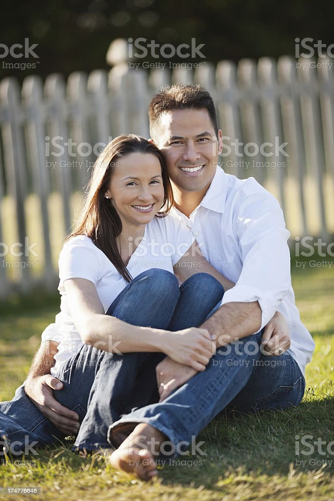 Happy Mid Adult Couple Sitting On Grass At Park royalty-free stock photo