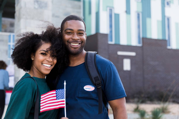 Happy mid adult couple smiles for camera after voting After they voted, the happy mid adult couple smiles for the camera.  The wife holds and flag and the husband wears an