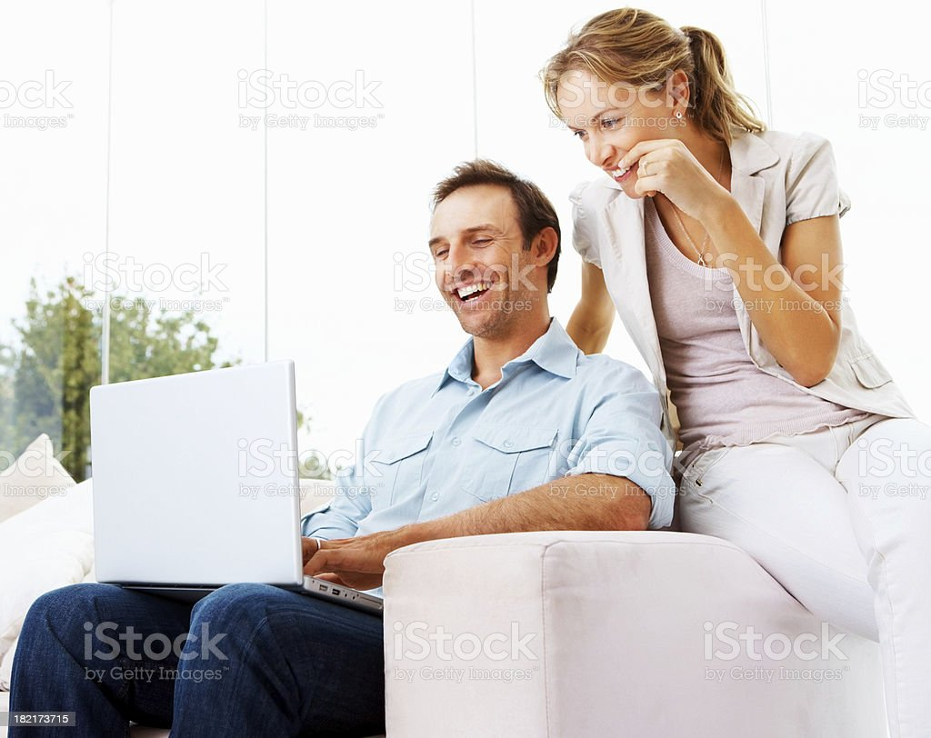 Happy mid adult couple using a laptop royalty-free stock photo
