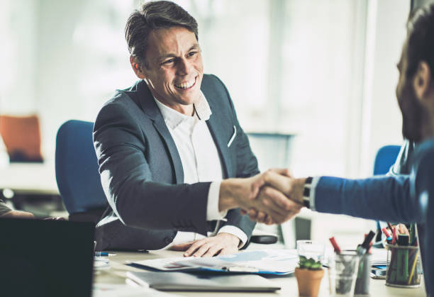 Happy mid adult insurance agent shaking hands with his customer in the office. Happy bank manager shaking hands with his customer in the office. happy boss stock pictures, royalty-free photos & images