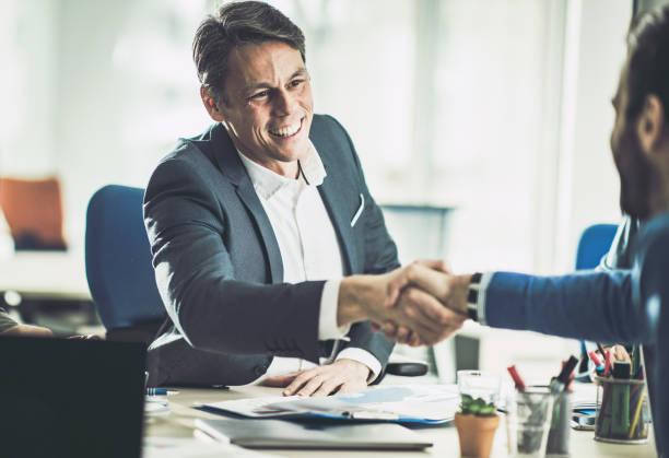 オフィスでお客様と握手をするハッピーミッドアダルト保険代理店。 - 投資家 ストックフォトと画像