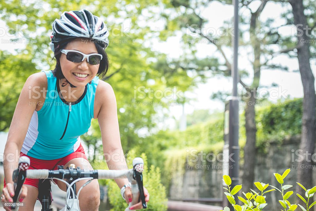 Happy Mid Adult Japanese Woman Riding Bike in Kyoto, Japan stock photo