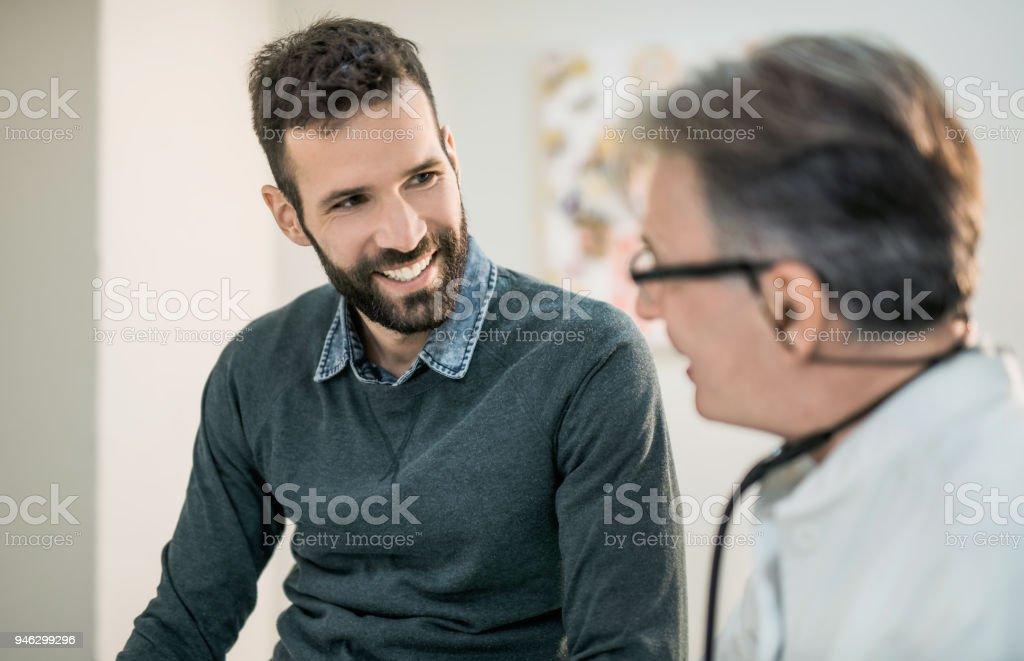 Glücklich Mitte erwachsenen männlichen Patienten im Gespräch mit seinem Arzt. - Lizenzfrei Arzt Stock-Foto