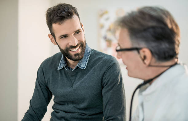 happy mid adult male patient talking with his doctor. - males stock pictures, royalty-free photos & images