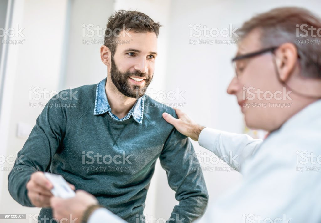 Happy mid adult man receiving a medicine from his doctor. stock photo