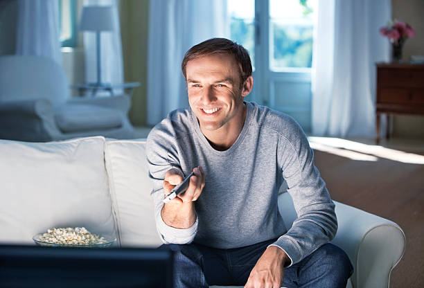 Happy mid adult man sitting on sofa with a remote control stock photo
