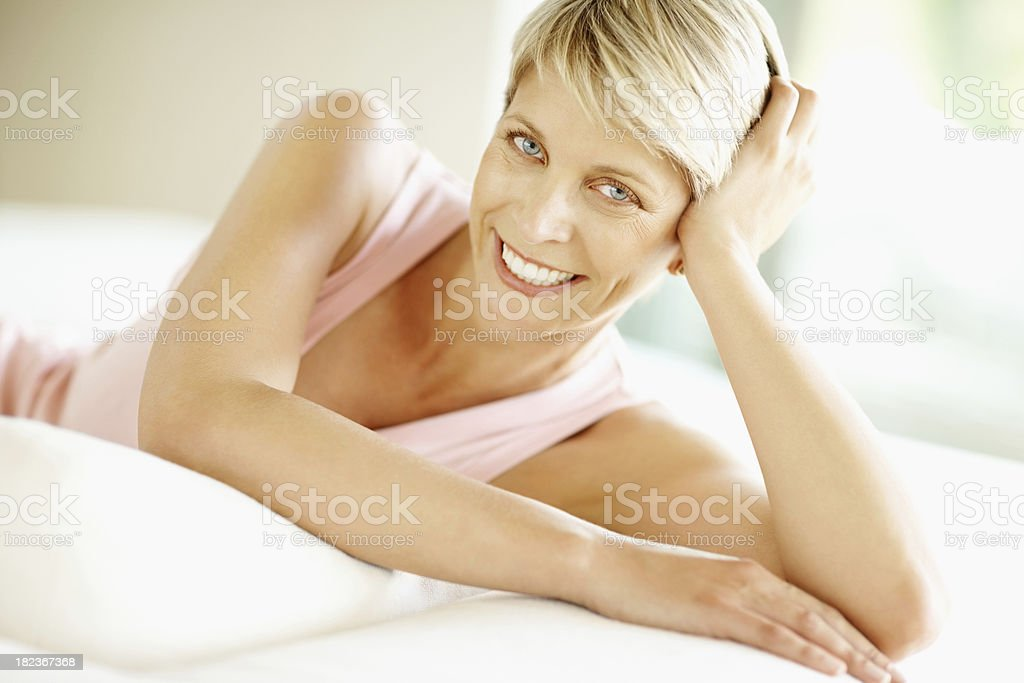 Happy mid adult woman relaxing on bed stock photo