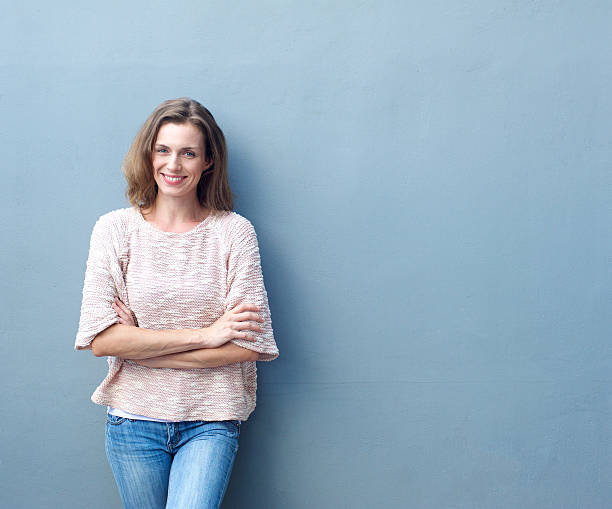 Happy mid adult woman smiling with arms crossed stock photo