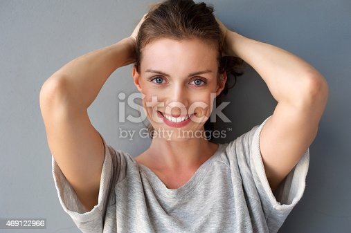 istock Happy mid adult woman smiling with hands in hair 469122966