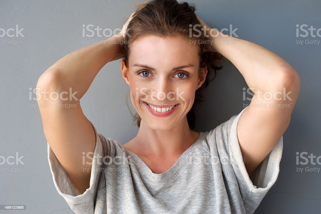 Happy mid adult woman smiling with hands in hair stock photo