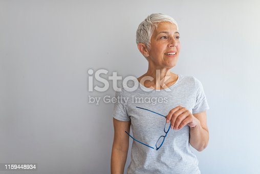 istock Happy mid woman against grey background with copy space 1159448934