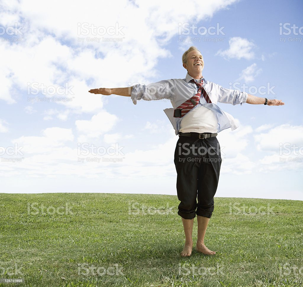 Happy mid-age man with arms wide open, smiling in an open field stock photo