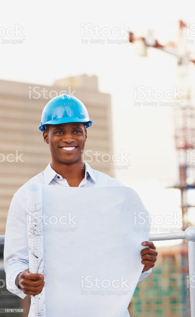 Happy middle aged architect holding blue print royalty-free stock photo
