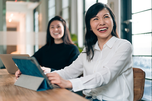 Happy middle aged Asian woman job attending retraining course