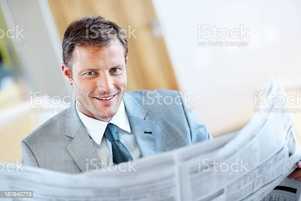Happy Middle Aged Business Man Reading Newspaper Stock Photo - Download Image Now