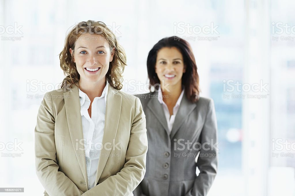 Happy middle aged business woman with colleague in background royalty-free stock photo