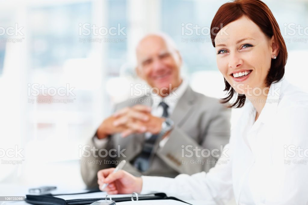 Happy middle aged business woman with manager in background royalty-free stock photo