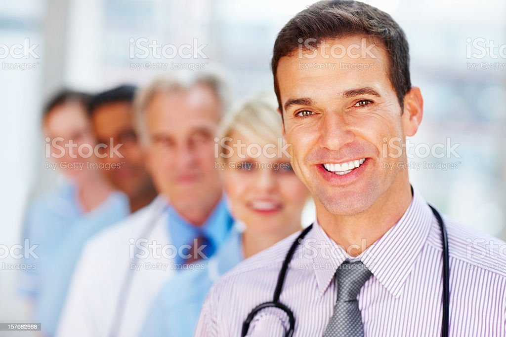 Happy, middle aged doctor standing in front of his team royalty-free stock photo