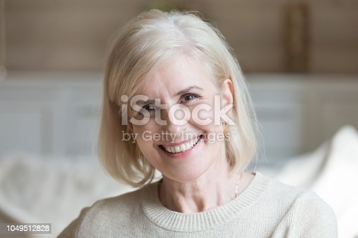 istock Happy middle aged elderly grey haired woman looking at camera 1049512828