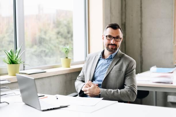 Glücklich Mitte Alter schön Geschäftsmann im Hemd auf Laptop-Computer im Büro arbeiten. – Foto