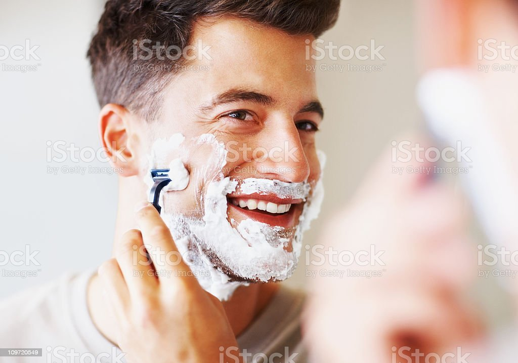 Happy middle aged man using razor to shave stock photo