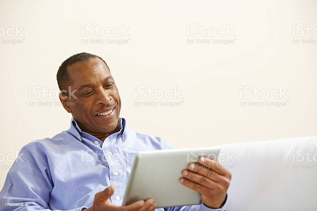 Happy middle aged man watching something on his digital tablet stock photo