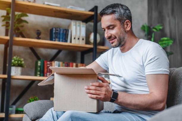 glücklicher mann mittleren alters mit pappkartons lieferung zu hause - bekommen stock-fotos und bilder