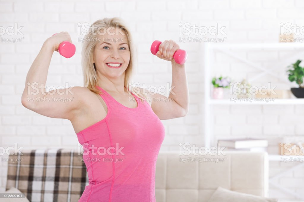 Happy middle aged woman lifting dumbbells at home in the living room stock photo