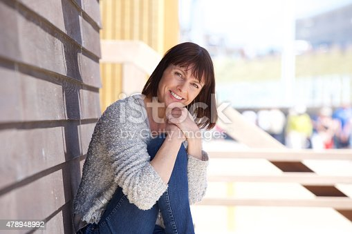 825083304 istock photo Happy middle aged woman sitting outside 478948992