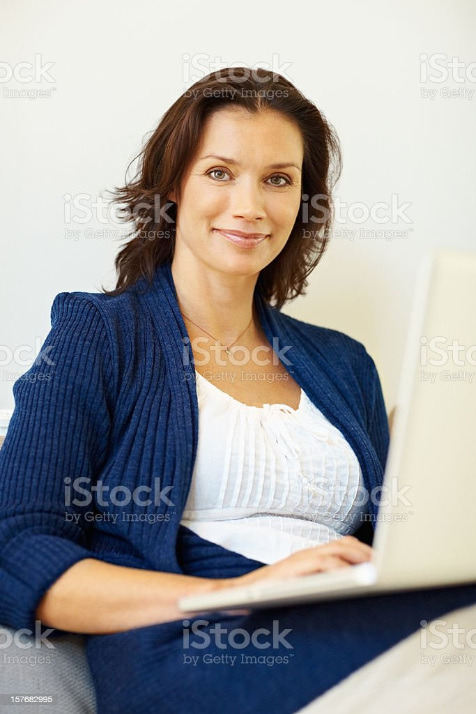 Happy middle aged woman working on a laptop royalty-free stock photo
