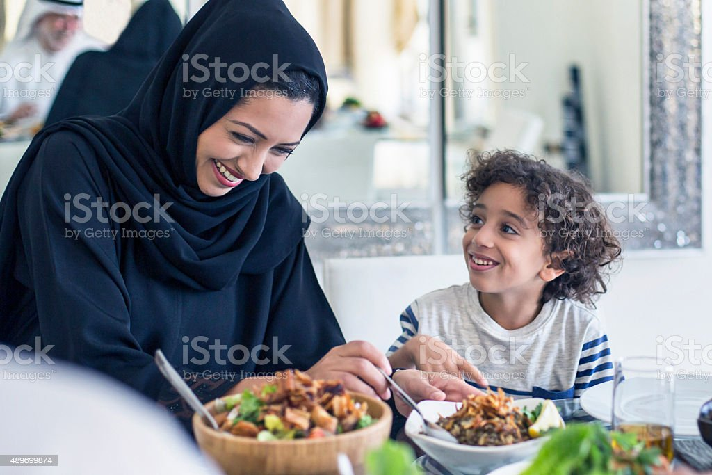 Happy middle Eastern mother and son having lunch stock photo