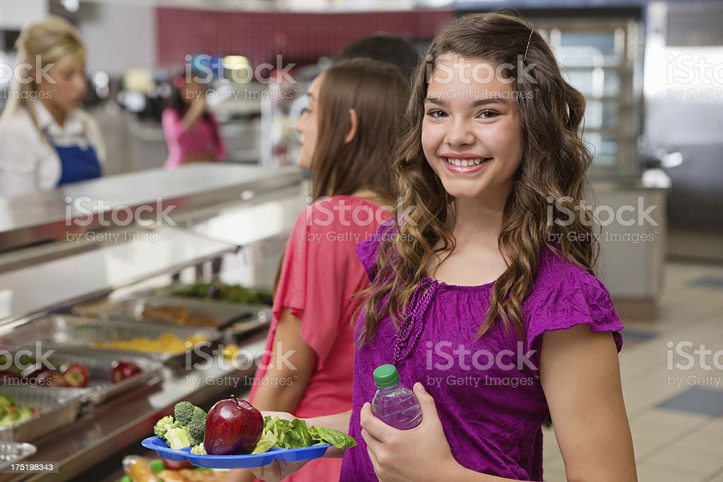 Happy middle school girl making healthy lunch lines in cafeteria royalty-free stock photo