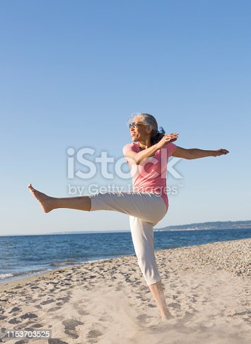 Happy, middle-aged, black, African American woman wearing sunglasses having fun on the beach in summer. Active, healthy, mature lifestyles.