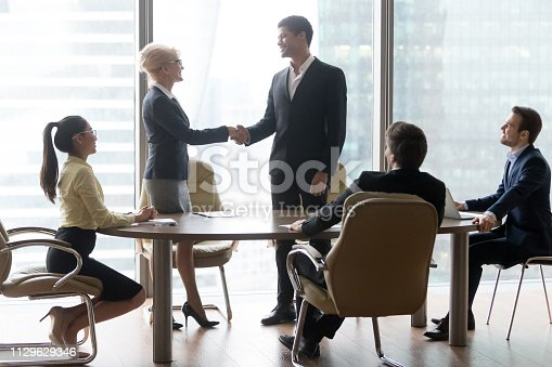 istock Happy middle-aged boss handshaking welcoming new partner at team meeting 1129629346