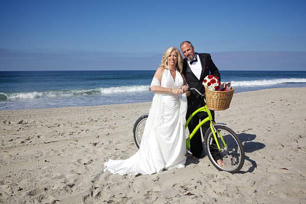 glückliche mittleren alter braut und bräutigam am strand mit dem fahrrad - hochzeitskleid über 50 stock-fotos und bilder