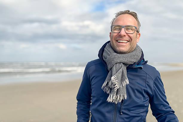 happy middle-aged man on an autumn beach - wollschal stock-fotos und bilder