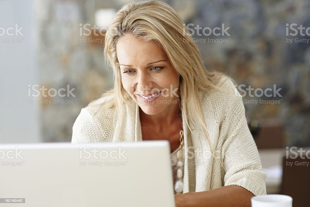 Happy, middle-aged woman using a laptop stock photo