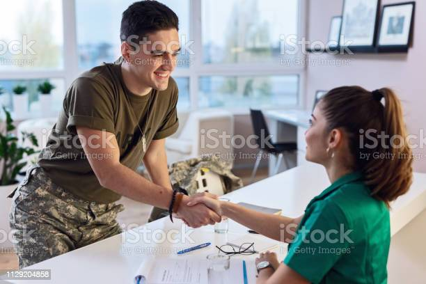 Happy military man shaking hands with female doctor at clinic picture id1129204858?b=1&k=6&m=1129204858&s=612x612&h=da0xp1occjvh9slvv vts3huk 3xpwtdwsy zu0iklw=