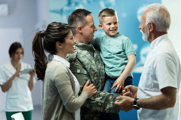 Happy military officer with his family communicating with doctor in the hospital. Happy senior doctor talking to little boy who came with mother and military father at clinic. Focus is on military man. military lifestyle stock pictures, royalty-free photos & images