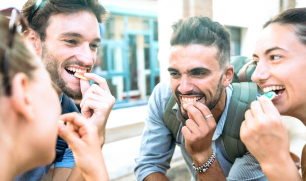 Happy millenial friends having fun at city center eating sugar candies - Z generation friendship concept with young millenial people hanging out together - Guys and girls on youth lifestyle mood stock photo
