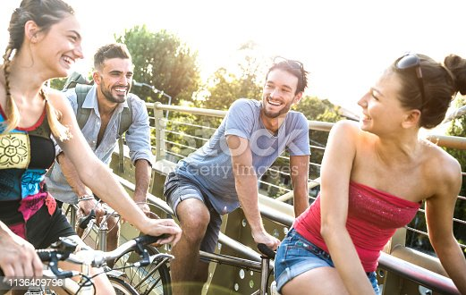Happy millenial friends having fun riding bicycle in city park - Friendship concept with young millennial people students biking together to university college campus - Bright vivid retro filter