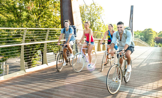 Happy millenial friends having fun riding bike at city park - Friendship concept with young millennial students biking together on bicycle lane - Bright late afternoon filter with sunshine halo stock photo