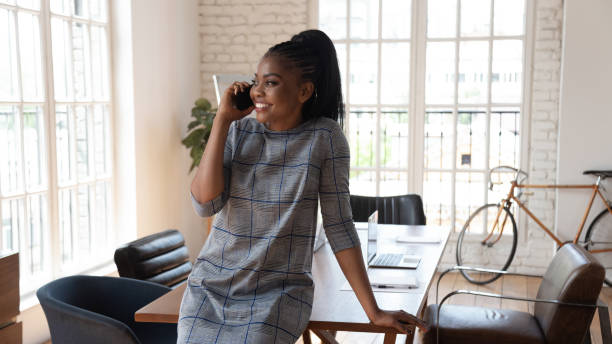 Happy millennial african american female manager talking on mobile phone. Happy millennial african american female manager standing at modern creative office, talking on mobile phone with partners, negotiating with clients, consulting customers or solving business issues. bingo caller stock pictures, royalty-free photos & images