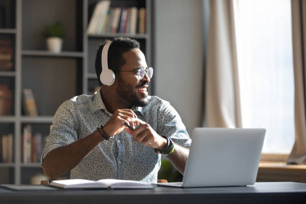 Happy millennial african businessman wear headphones listening music in office Happy relaxed millennial afro american business man wear wireless headphones look away rest at workplace finished work listening music podcast feel peace of mind concept sit at desk in sunny office listening stock pictures, royalty-free photos & images
