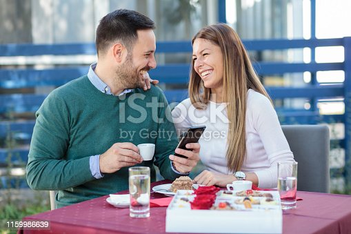 Smiling happy millennial couple celebrating anniversary or birthday in a restaurant. Eating cake and drinking coffee.