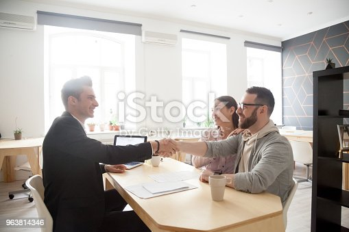 963814372istockphoto Happy millennial couple handshaking smiling financial advisor, lawyer or realtor 963814346