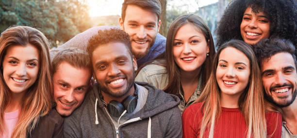 happy millennial friends from diverse cultures and races having fun posing in front of smartphone camera - youth and friendship concept - young multiracial people smiling - main focus on african man - young adults hanging out stock pictures, royalty-free photos & images