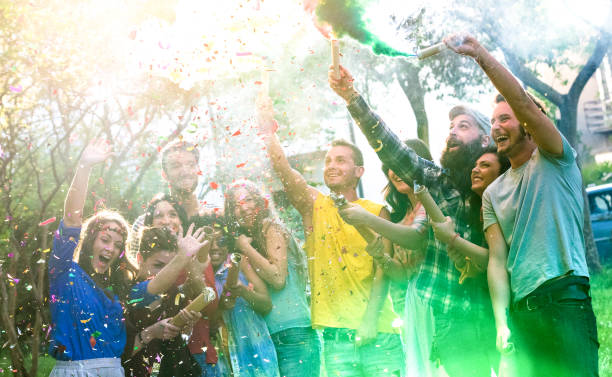 Happy millennial friends having fun at garden party with multicolored smoke bombs outside - Young millenial students celebrating spring break fest together on genuine youth concept - Focus on confetti stock photo