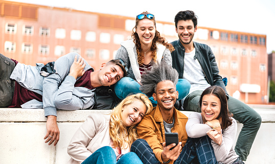 Happy millennial friends having fun with mobile phone after lockdown reopening - Joyful guys and girls spending fancy time together at university college break - Warm bright filter